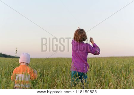Two Girls Flying Their Kite In A Field