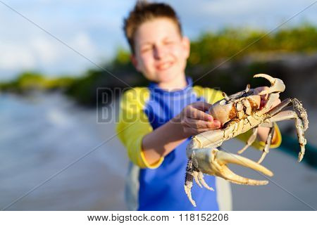 Teen age boy holding big crab at beach