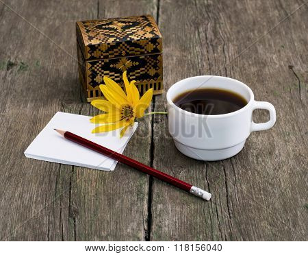 Pencil, Coffee And The Casket Decorated With A Yellow Flower