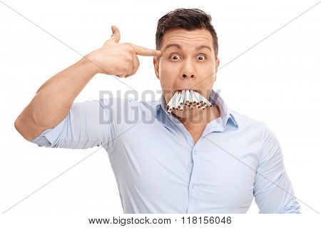 Studio shot of a man with a bunch of cigarettes in his mouth holding a hand gun against his head isolated on white background