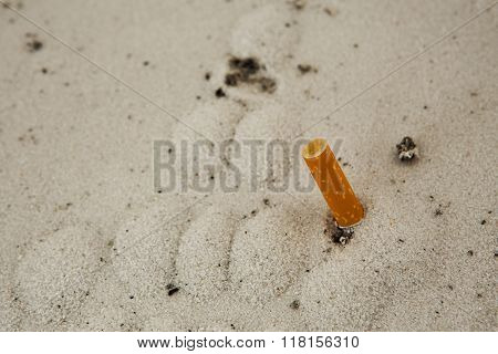 A cigarette in sand ashtray on background