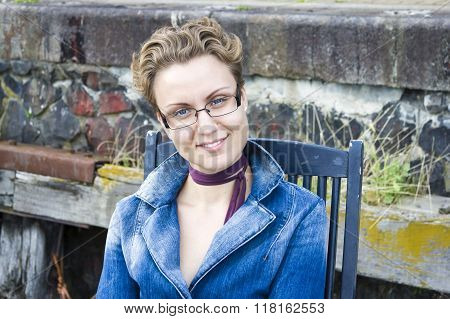 Young Woman In Glasses Sitting In Profile