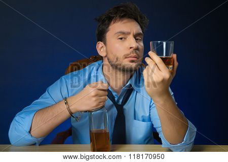 Drunk man drinking alcohol at the table