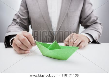 Businessman at desk with a green paper origami boat, concept for aspirations, leadership, strategy or just boredom in the office