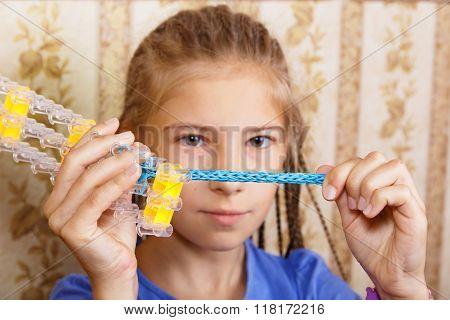 Girl Considers A Homemade Bracelet