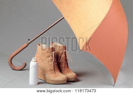 Brown Suede Boots Under An Umbrella On A Gray Background. Waterproof Treatment For Suede Boots Conce