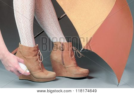 Female Legs In Brown Suede Boots Under An Umbrella On A Gray Background. Waterproof Treatment For Su