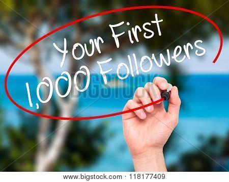 Man Hand Writing Your First 1,000 Followers  With Black Marker On Visual Screen