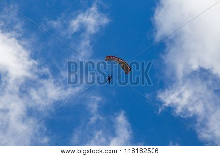 Skydiver Comes Down From The Sky Between The Clouds