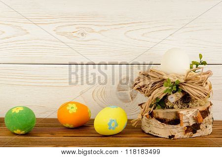 Easter arrangement and easter eggs on wooden background.