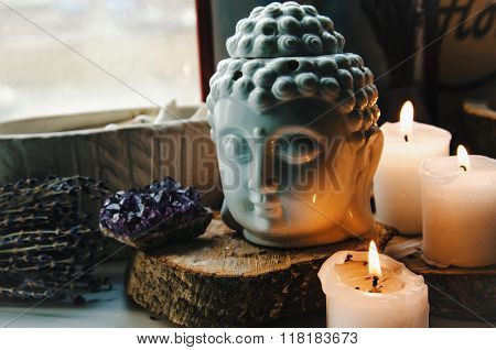 spiritual ritual meditation face of Buddha ametist candles on old wooden background