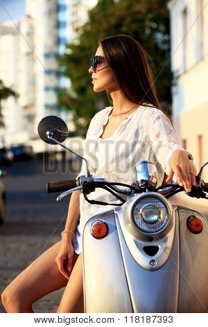 Portrait of a beautiful girl sitting on silver retro scooter, smiling and looking at the camera