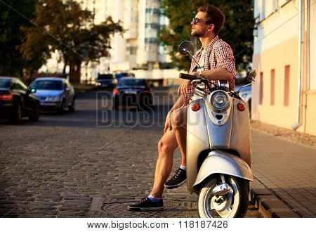 fashionable young man riding a vintage scooter in street