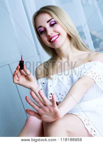 pretty woman with bright pink makeup applying nail polish