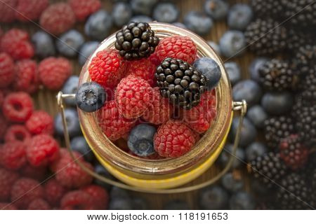 different berries (blueberries raspberries blackberries) in a basket on a wooden table flat lay
