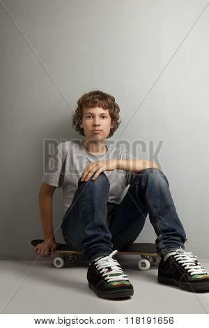 happy boy sitting on skateboard