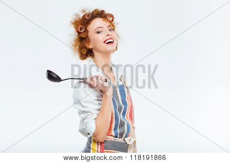 Smiling redhead housewife with curly hair in apron holding soup ladle isolated on a white background