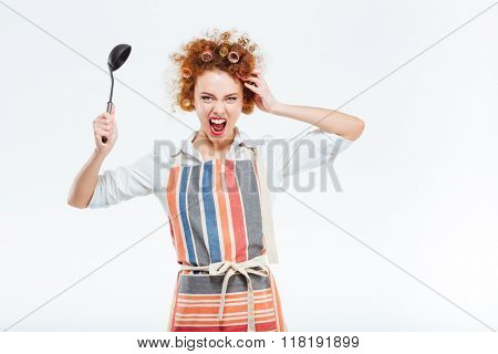 Crazy redhead housewife with curly hair in apron holding soup ladle and screaming isolated on a white background