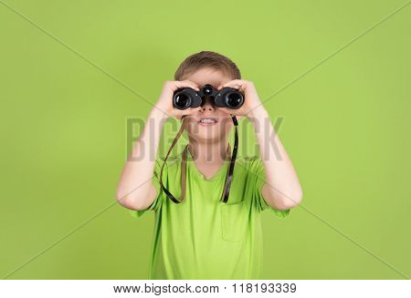 Boy with binoculars isolated on green background with copyspace. Kid looking through binoculars.
