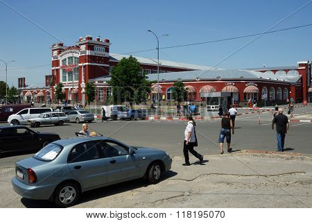 KHARKOV, UKRAINE - JUNE 5, 2014: People on the square in front of Central Farmer's Market. The building was erected in 1912-1914 by design of M. Zagoskin