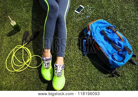 Sporty Woman Sitting On The Green Grass