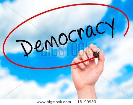 Man Hand Writing Democracy With Black Marker On Visual Screen