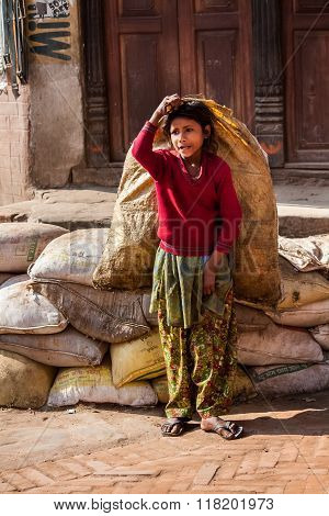 Bhaktapur, Nepal - April 19, 2013: Child Labour In Asia.poorly Dressed Teen Girl Drags The Heavy Bag