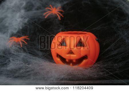 Plastic pumpkin with spiderwebs in the background