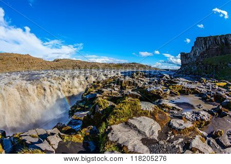 Colossal Dettifoss waterfall in Iceland. Sunset on a summer day,  magnificent rainbow in the water foam