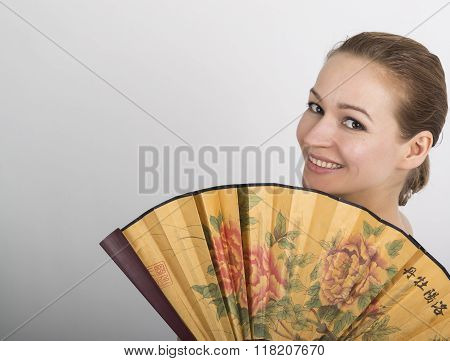 close up portrait of a beautiful brunette woman covers half the face beautiful fan