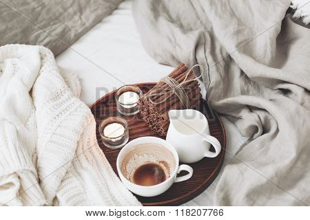 Wooden tray with coffee, milk, cinnamon sticks and tea candles in the bed, lazy morning, warm winter mood