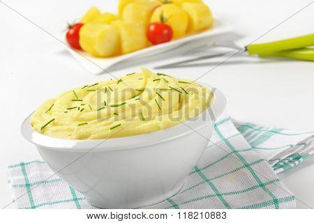 bowl of mashed potato puree with chopped chives on checkered dishtowel - close up