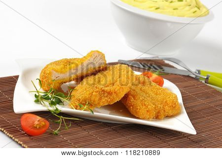 bowl of mashed potato puree and plate of breaded turkey breast on brown place mat - close up