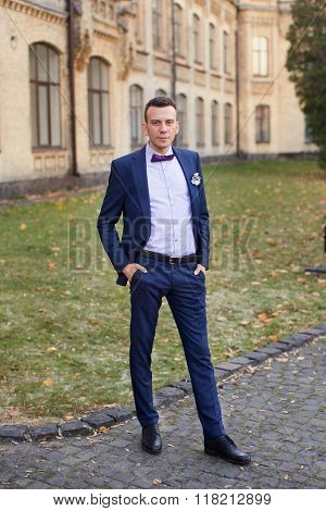 stylish trendy confident happy groom in blue bow  and cute suit