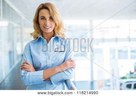 Portrait of young businesswoman. Young receptionist looking at camera and standing in nice modern building. Office interior