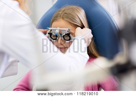Girl controls eyesight at eye doctor in clinic