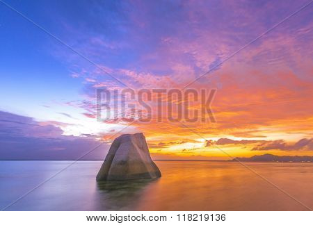 Lonely rock reflecting in the sea during beautiful vibrant sunset. Island of La Digue, Seychelles