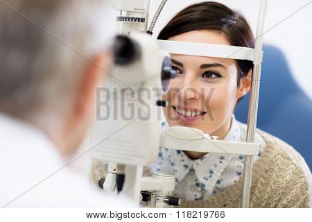 Dark hear woman look in ophthalmoscope to determine diopter in clinic