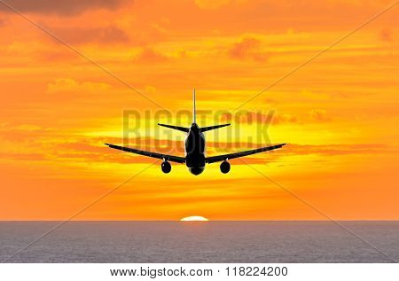 Sunset or sunrise (dawn, dusk ) flight of the airplane (jet) over beautiful sky and ocean.