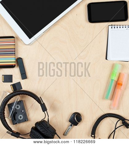 Flat lay office tools and supplies, tablet computer,audio headphone cards and other stuff. Flat design and top view on desk as frame with blank center on wood background.