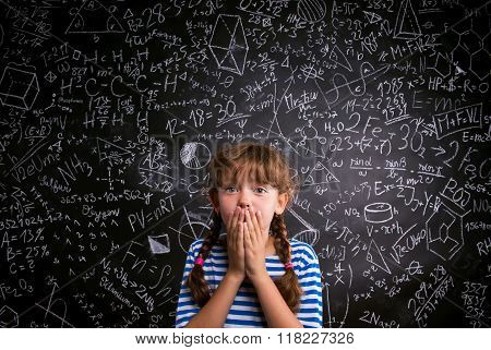 Surprised girl, hands on mouth, blackboard with mathematical sym