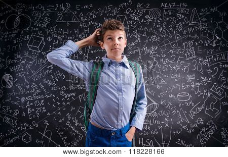 Boy  thinking, scratching his head, blackboard with mathematical