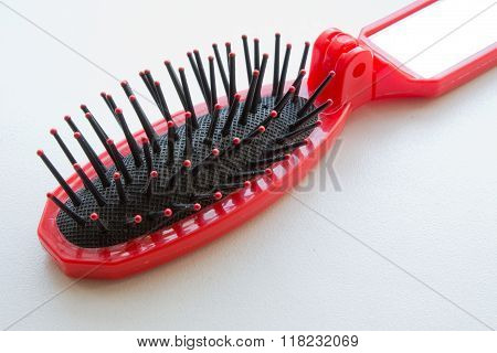 Red hairbrush closeup on white background