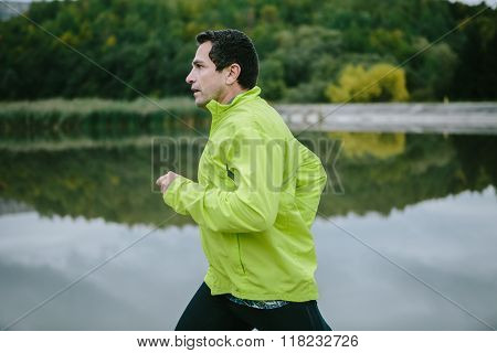 Man in yellow neon jacket runnig at the lake