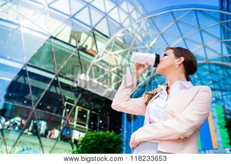 Businesswoman drinking coffee from thermo cup against  office bu