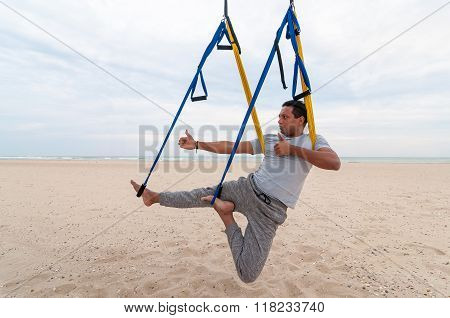 Anti-gravity Yoga, man doing yoga exercises or fly-yoga on the sea background