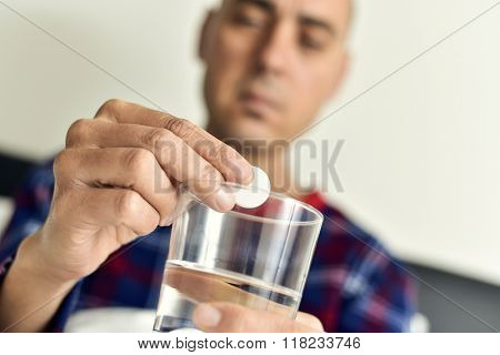closeup of a young caucasian man in pajamas in bed about to put an effervescent tablet into a glass with water