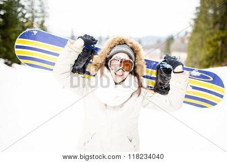 Beautiful girl in winter forest with snowboard and ski mask.Girl snowboarding in the mountains on sk