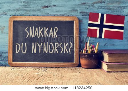 a chalkboard with the question snakkar du nynorsk?, do you speak Norwegian? written in Norwegian, a pot with pencils, some books and the flag of Norway, on a wooden desk