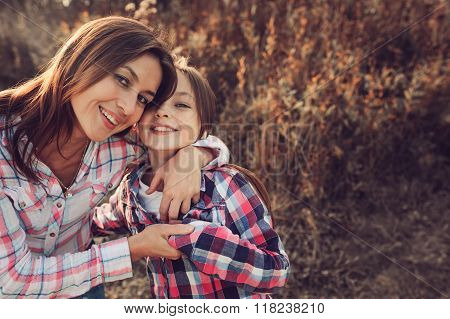 happy mother and daughter on the walk on summer field. Family spending vacation outdoor